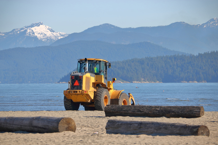 A large bulldozer is used to clean up the beach on a scenic part of Canada's west coast.