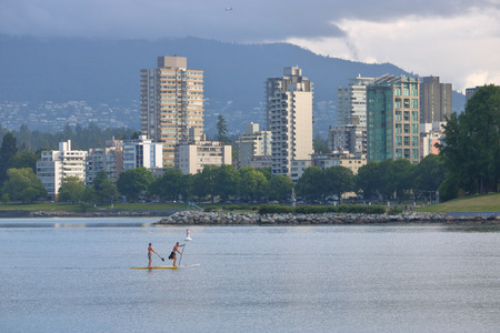 Two paddle boarders enjoy a relaxing excursion on English Bay in Vancouver, British Columbia on June 9, 2017. Editorial