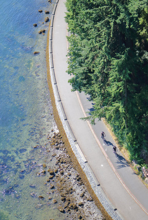 A high angle, vertical view of cyclists on the Stanley Park seawall in Vancouver, British Columbia, Canada.