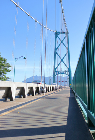 A low angle, vertical view of the Lions Gate or First Narrows walkway for pedestrians and the tall supporting arch with cables.