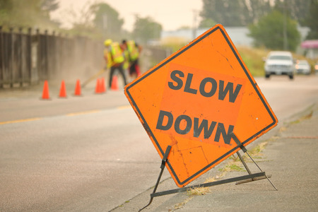 A large, English construction sign reminds motorists to slow down while road construction is underway. Stock Photo