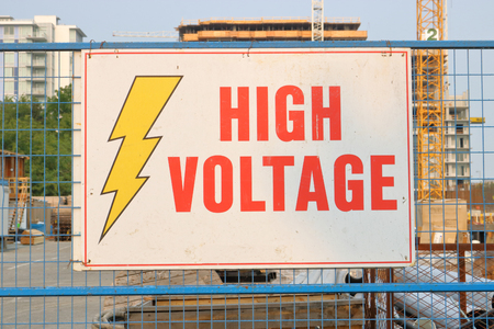 A sign on a construction site warns that there is high voltage in the area.