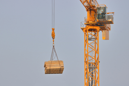 A high tower construction crane is used to move a heavy pack of lumber.