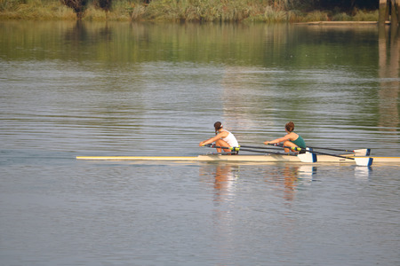 Two female scullers practice on the water.