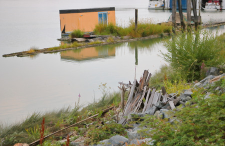 Various shelters for the homeless including an industrial storage bin and a lean-to comprised of strips of wood, are found on the river.