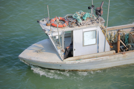 High angle view of a metal utility boat used for retrieving stray logs on a river, moves right to left. Stock Photo