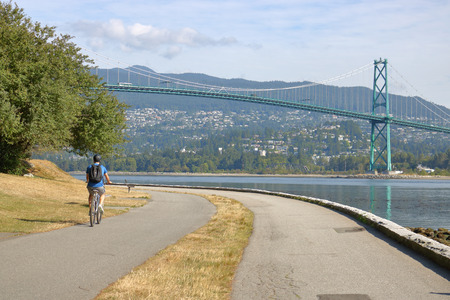 A lane encircles Vancouver, Canadas Stanley Park that cyclists can enjoy with a magnificent view of the city and the Lions Gate Bridge.