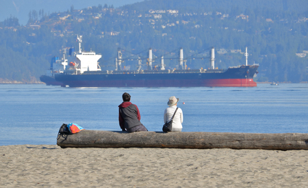 A couple sit together on a sandy beach watching freighters in the harbor. Stock Photo