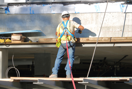 A construction worker uses a cable and harness attached to his body to provide safe conditions when working in an elevated environment.
