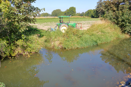 A large, deep ditch is used to store water that can be pumped out during the dry season to irrigate farm crops.