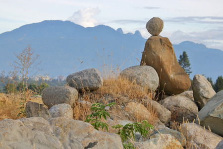 With creative flare, a person has balanced rocks in a pit to represent a person looking at Vancouvers twin peaks, or Lions on the North Shore Mountain range.