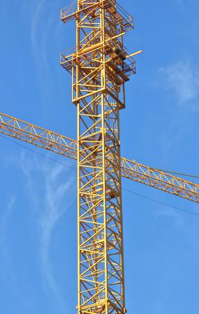 Dicht gedetailleerd verticaal schot van torenkranen en de gebruikte infrastructuur om het te assembleren. Stockfoto