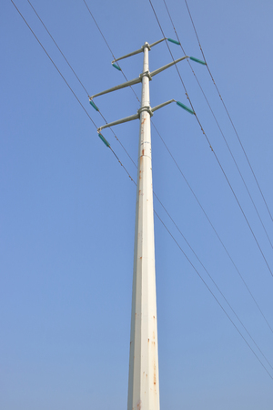 A major power line distributed to the city is supported by a tall, metal pole. Stock Photo