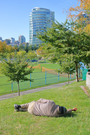 A homeless person sleeps on a knoll overlooking a park in Vancouver, Canada, one of the most expensive cities in the world to live in.