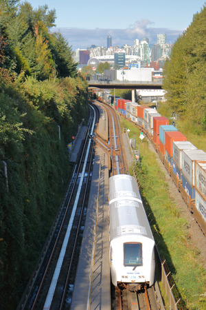 High angle view of Skytrain, a public transit system as it passes traditional rail service in Vancouver, BC, Canada on October 1, 2017.