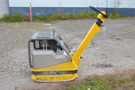Profile view of a one man compactor used to harden and compact earth or soil.