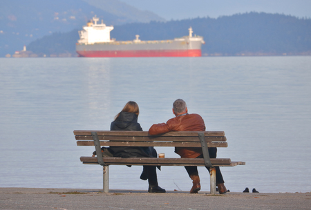 A couple share time together sitting on a bench overlooking freighters on the sea coast.
