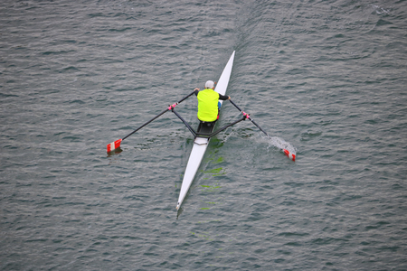 High angle view of a single person sculling with two oars extended in the water. Stock Photo