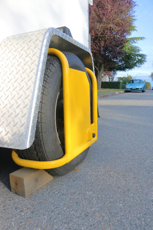 A tire wheel choke or wheel lock is used to ensure a trailer or vehicle attachment can not be stolen. Stock Photo