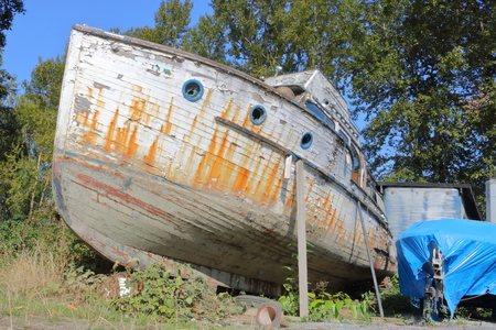 With its paint peeling and hull in disrepair, a wooden boat, forgotten and abandoned, sits cradled on supports. Stock Photo