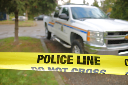 Police tape is used to secure a crime scene where officers can investigate a recent homicide without contaminating the area. Stock Photo