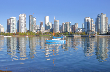 A beautiful sunny morning with a single sailboat and False Creek reflecting the many modern condominiums in the downtown core. Stock Photo