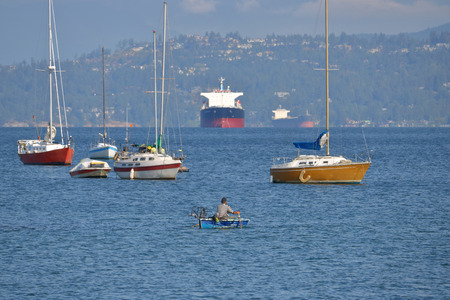 A rowboat, sailboats and freighter are the wide variety of boats found in a typical harbor. Stock Photo