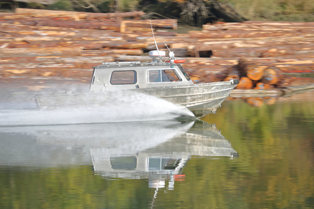 A small metal boat speeds across a smooth, reflective water surface.