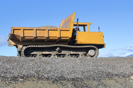 A dumper vehicle is used for moving and carrying loads of soil or heavy material on a construction site.