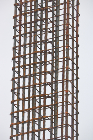 A vertical, isolated view of wired reinforcing bar that is being used on a construction site.