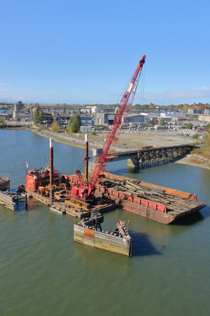 Heavy industrial equipment is used to install pylons along a railway track crossing the Fraser River in Vancouver, British Columbia on October 17, 2017.