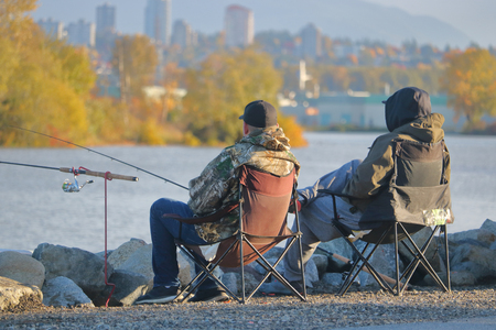 Relaxed and dressed for the cooler Fall weather, two male fishermen spend a leisurely morning fishing beside a river.