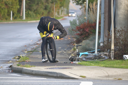 A cyclist is faced with the nuisance of fixing a flat tire on his bicycle. Stock Photo