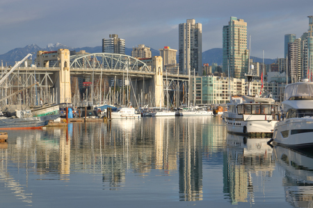 Vancouver, Canada and a cityscape including the Burrard Street Bridge, marina and hi rise condominiums in the west end area.