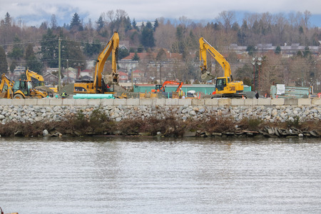 Heavy machinery is used in south Vancouver, Canada to build and reinforce the Fraser riverbank on January 10, 2018. Éditoriale