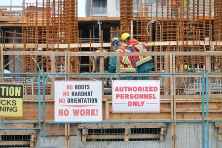 Workers adhere to rules and regulations posted on the construction site.