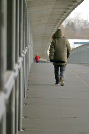 A pedestrian uses the protective over-hang on a city bridge to protect against the winter weather conditions.