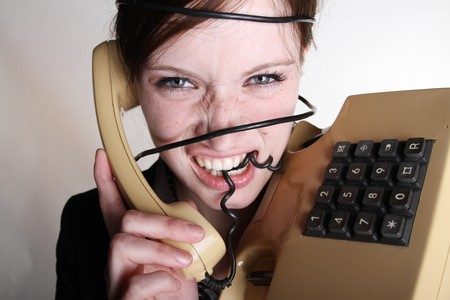 annoyance: A woman has annoyance with her telephone