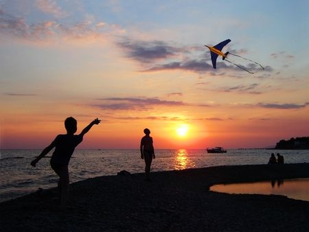 The sea landscape with the sunset. Boy flying a kite Stock Photo - 6096481