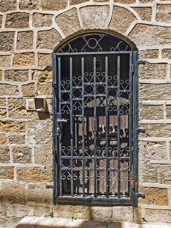 jaffa: Old wooden door closed by a metal lattice in old Jaffa, Israel Stock Photo