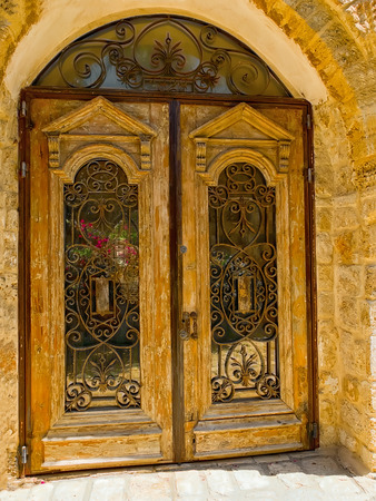 Old wooden door with a lattice and glasses in Jaffa, Israel photo