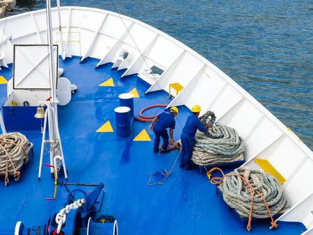 全体的な青と黄色のヘルメット作業ロープと船の青デッキ操作を係留中に身に着けている船員をデッキします。