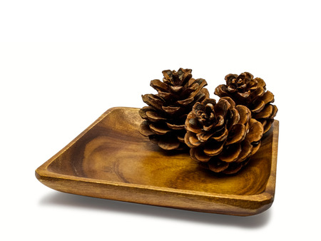 pinecones: Wooden plate with pinecones isolated on white.