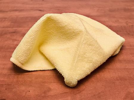 dishcloth: Closeup of a yellow microfiber dishcloth on a table