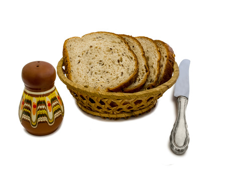 salt shaker: Slices of bread in a basket, salt shaker and knife isolated on white background