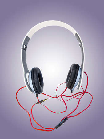 noise isolation: Stereo headphones with red cable plug against purple background.