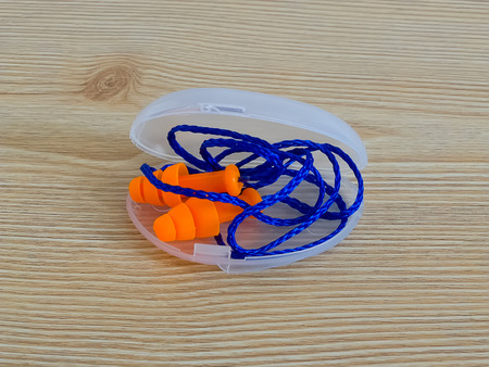 muffle: Earplugs in their box on wooden background