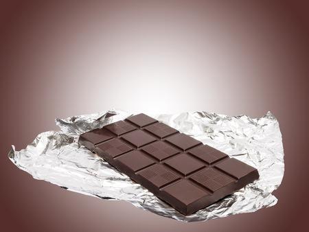 Chocoladereep met folie tegen de bruine achtergrond Stockfoto