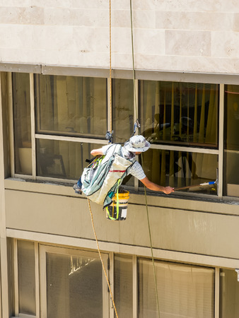window washer: Professional window washer cleaning windows on a building.