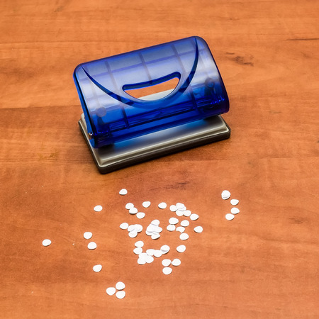 punch press: Blue office puncher with confetti on a desk.